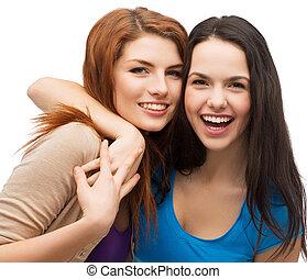 Dvě smějící holky se objímají