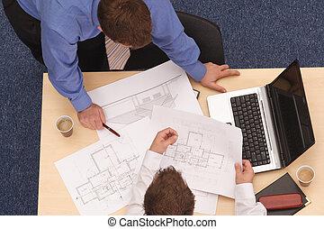 Dva architekti, kteří prohlížejí plány