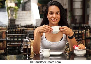 Holka pije kafe v kavárně