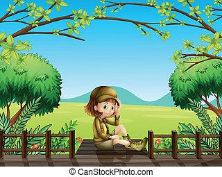 Holka sedící u dřevěného mostu
