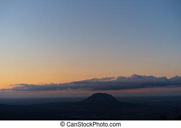 Horská krajina. Panoramický pohled na hory proti obloze při západu slunce