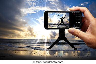 Kameraový telefon a šťastný skokan na pláži