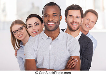 Konfidentní obchodní tým. Drazí afričtí muži drží ruce nad hlavou a usmívají se, zatímco skupina lidí, kteří stojí za ním v řadě a dívají se na kameru