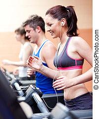Krásná žena, která stojí na běžícím stroji a poslouchá hudbu ve fitness centru