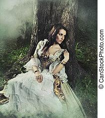 Krásná bruneta v prastarých šatech v lese