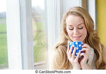 Krásná mladá žena pije čaj
