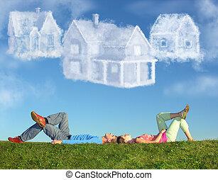 Ležící pár na trávě a sní o třech mrakech