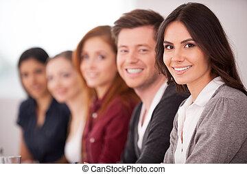 Lidé na semináři. Atraktivní mladá žena, která se směje před kamerou zatímco ostatní sedí za ní