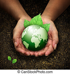 Lidské ruce drží zelenou zemi