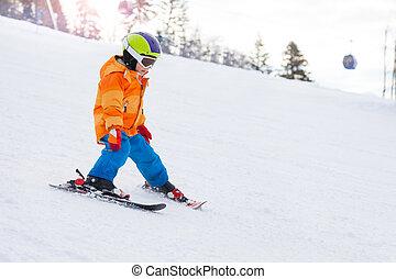 Lyžařský chlapec v lyžařské masce, helma na horské svahě