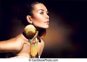 Módní portrét. Zlaté klenoty. Ztřeštěný makeup