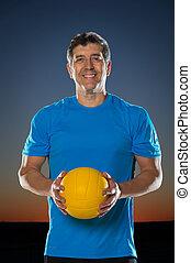Mature hispánec drží volejbal