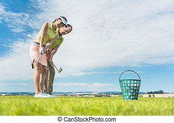 Mladá žena, co cvičí golfovou houpačku, pomáhala svému instruktorovi