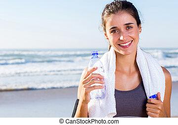 Mladá žena, co pije vodu po cvičení