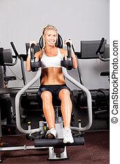 Mladá žena cvičí v tělocvičně s kuličkou