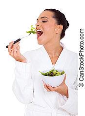 Mladá žena jí zdravý salát