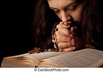 Mladá žena, která se modlí na bibli s růženeckou