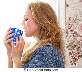 Mladá žena pije čaj