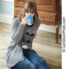Mladá žena pije kávu