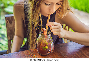 Mladá žena pije studený čaj se skořicí v rýžovém poli