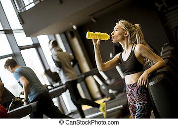 Mladá žena pije v tělocvičně po cvičení