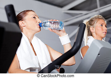 Mladá žena pije vodu, když cvičí