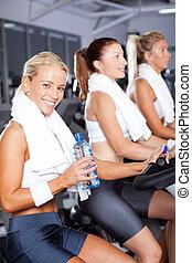 Mladá žena pije vodu, když cykluje v tělocvičně