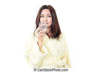 Mladá žena pije vodu