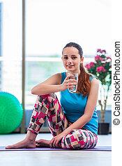 Mladá žena pije vodu v tělocvičně