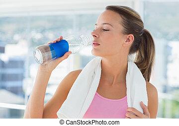 Mladá žena pila vodu v tělocvičně
