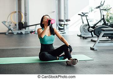 Mladá žena pila vodu v tělocvičně.