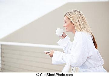 Mladá žena v županu pije kávu