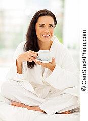 Mladá žena v pyžamu pije kávu