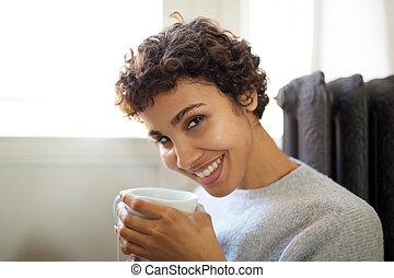 Mladá afričanská americká žena pije horký čaj ze šálku