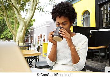 Mladá africká žena pije čaj