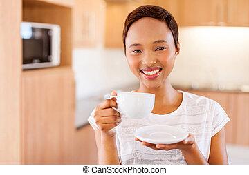 Mladá africká žena pije kávu v kuchyni