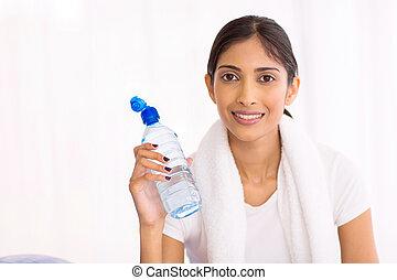 Mladá indická žena po cvičení pila vodu