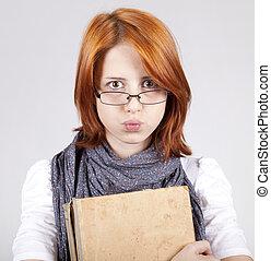 Mladé pochybné děvče v brýlích se starými knihami