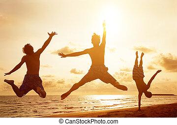 Mladí lidé skákají na pláži se západem slunce