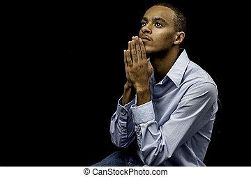 Mladý černý muž se modlí