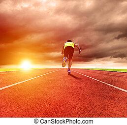 Mladý muž běžící po dráze s úsvitem slunce