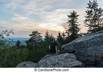 Mladý muž sedící na kamenném skále v krajině s stromy při západu slunce