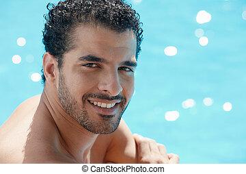 Mladý muž sedící v bazénu