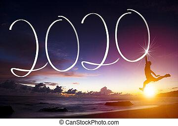 Mladý muž skáče na pláži. Šťastný nový rok 2020