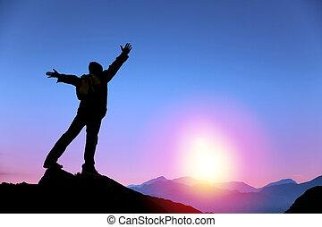 Mladý muž stojí na vrcholu hory a dívá se na východ slunce