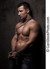 Mladý mužský model si dobře staví řetězy nad svým tělem