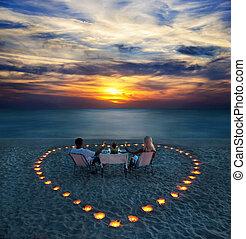 Mladý pár má romantickou večeři na pláži