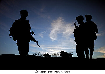 Moderní vojáci ve středním siluetu, proti slunci, s vozidlem v pozadí