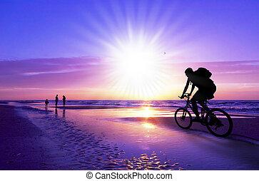 Mountain motorkář na pláži a západ slunce