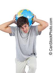 Muž drží glóbus na zádech